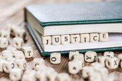Rechtvaardigheidswoord op een houten blok wordt geschreven dat royalty-vrije stock foto's