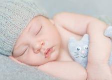 Recién nacido dulce en sombrero gris con el juguete Foto de archivo libre de regalías