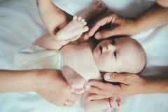 Recién nacido en manos que cuidan Cuidado recién nacido del bebé Bebé o masaje dado muchacho Cuidado pediátrico para la salud de  foto de archivo