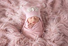 Recién nacido en sombrero de la gorrita tejida en una alfombra lanuda fotografía de archivo