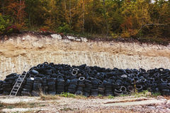 Reciclagem do pneu de borracha os pneus de carro usado velhos em um cemitério de automóveis nas pilhas que esperam reciclam imagens de stock