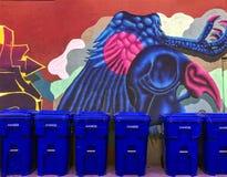 Reciclando compartimientos azules se alineó contra mural colorido de la pared de la criatura azul grande imagenes de archivo
