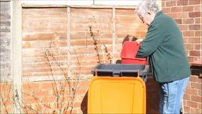 Reciclando desperdicios en un compartimiento del bote de basura o de los desperdicios almacen de video