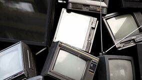 Recicle el concepto - desperdicios electrónicos de la televisión vieja, basura, desperdicios demostración apilada TV quebrada en  almacen de metraje de vídeo