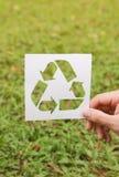 Recicle el símbolo en fondo de la hierba verde Foto de archivo