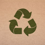 Recicle el símbolo en un fondo de lino imagenes de archivo