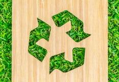 Recicle o sinal cortado na placa de madeira na grama Fotos de Stock Royalty Free