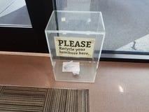 Recicle por favor su muestra del folleto aquí en la caja plástica fotos de archivo libres de regalías