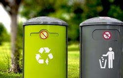 Recicle y los cubos de la basura en foco con un fondo borroso Imagen de archivo