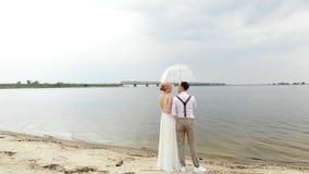 Recienes casados aero-, hermosos que se oponen en la playa, debajo de un paraguas transparente, al cielo azul, al río, y a un gra almacen de metraje de vídeo