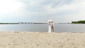 Recienes casados aero-, hermosos que se oponen en la playa, debajo de un paraguas transparente, al cielo azul, al r?o, y a un gra metrajes