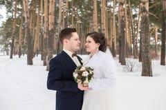 Recienes casados de los pares que caminan en un bosque del invierno Foto de archivo libre de regalías