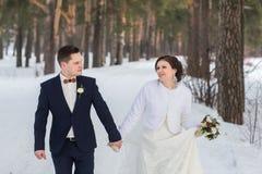 Recienes casados de los pares que caminan en un bosque del invierno Fotografía de archivo