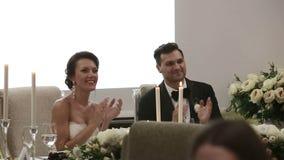 Recienes casados en la boda que se sienta en la tabla para haber aplaudido y una sonrisa festivos almacen de metraje de vídeo