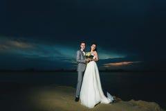 Recienes casados en la orilla del río en la noche Foto de archivo