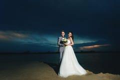 Recienes casados en la orilla del río en la noche Imagen de archivo