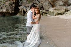 Recienes casados en la playa en la puesta del sol foto de archivo