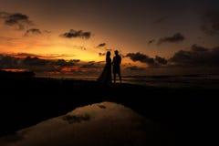 Recienes casados en la playa en la puesta del sol fotografía de archivo libre de regalías