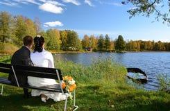 Recienes casados en un banco del lago Imagenes de archivo