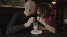 Recienes casados felices de los pares que se sientan en un café y un latte de consumición a partir de una taza almacen de video