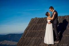 Recienes casados felices que abrazan en el tejado de la casa de campo Fondo maravilloso del paisaje de la montaña honeymoon Foto de archivo libre de regalías