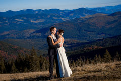Recienes casados felices que abrazan en el top de la montaña honeymoon imagen de archivo libre de regalías