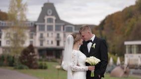 Recienes casados felices que caminan en el parque Novia y novio elegantes del handome afuera almacen de metraje de vídeo