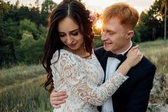 Recienes casados felices que se besan en la puesta del sol Fotos de archivo libres de regalías