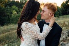 Recienes casados felices que se besan en la puesta del sol Imagenes de archivo
