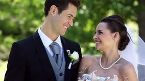 Recienes casados felices que se colocan al lado de su pastel de bodas almacen de metraje de vídeo
