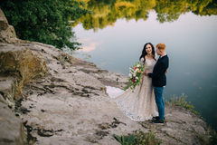 Recienes casados felices que se colocan en la orilla del río Imagenes de archivo