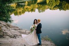 Recienes casados felices que se colocan en la orilla del río Fotografía de archivo libre de regalías