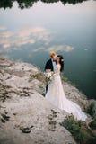 Recienes casados felices que se colocan en la orilla del río Fotos de archivo