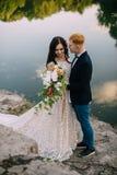 Recienes casados felices que se colocan en la orilla del río Foto de archivo