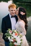 Recienes casados felices que se colocan en la orilla del río Fotografía de archivo