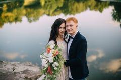 Recienes casados felices que se colocan en la orilla del río Imágenes de archivo libres de regalías