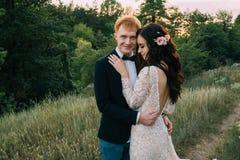 Recienes casados felices que se colocan y que abrazan Foto de archivo libre de regalías