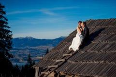 Recienes casados felices que se sientan en el tejado de la casa de campo Luna de miel en montañas Imágenes de archivo libres de regalías