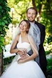 Recienes casados felices que sonríen, abarcamiento, presentando en parque Imagen de archivo libre de regalías