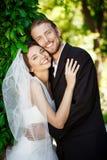 Recienes casados felices que sonríen, abarcamiento, presentando en parque Imagenes de archivo