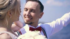 Recienes casados hermosos de los pares el retrato, el novio mira en el amor la novia, sonrisas, contra el mar y el cielo azules V almacen de metraje de vídeo