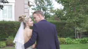 Recienes casados hermosos en los brazos que miran la cámara metrajes