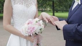Recienes casados jovenes que caminan afuera La novia y el novio caminan juntos en el parque en invierno o verano y las manos sost Fotos de archivo