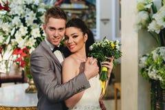 Recienes casados que abrazan en el fondo de flores Fotos de archivo libres de regalías