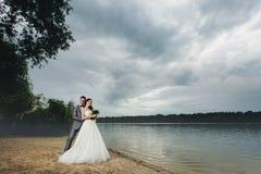 Recienes casados que abrazan en la orilla del río Fotografía de archivo libre de regalías