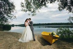 Recienes casados que llevan a cabo las manos cerca del barco Imagenes de archivo