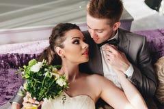 Recienes casados que mienten en el sofá Fotos de archivo