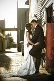 Recienes casados que se besan apasionado contra un rectángulo rojo Fotos de archivo libres de regalías
