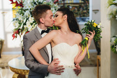 Recienes casados que se besan en el fondo de flores Fotos de archivo libres de regalías