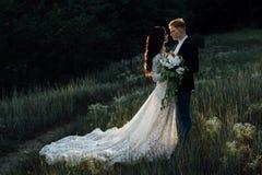 Recienes casados que se colocan y que abrazan al aire libre Imágenes de archivo libres de regalías